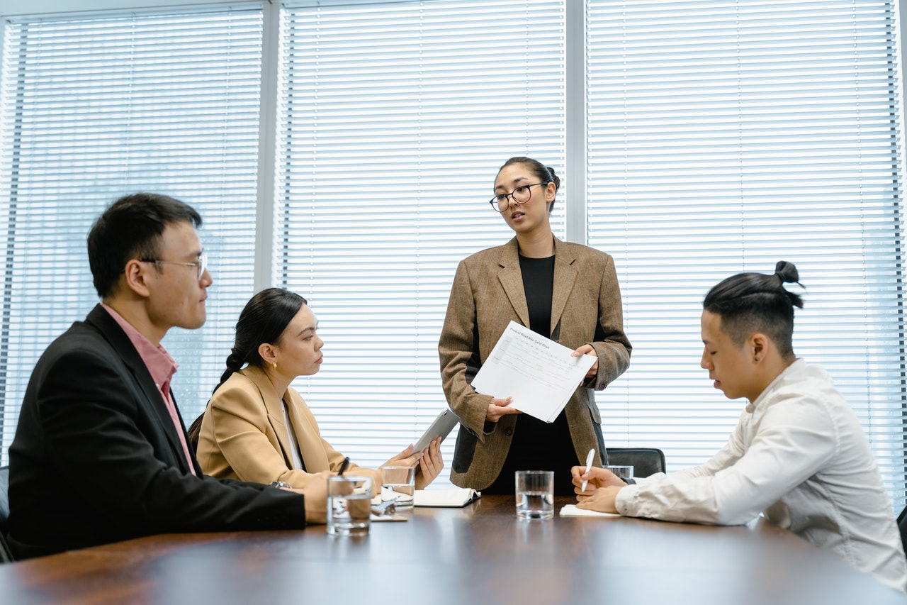 lady standing in meeting with document